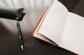 テーブルの上のノートとペンの写真・画像素材[3984553]
