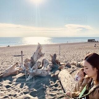 冬の海岸で日向ぼっこする親子の写真・画像素材[4007464]