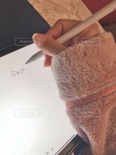 もこもこパジャマ姿で、タブレットに日記を書くの写真・画像素材[4120702]