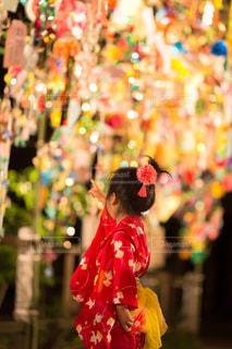 色とりどりの花の花瓶の横に立っている人の写真・画像素材[1291042]