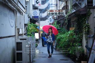 傘を持って歩道を歩いている人の写真・画像素材[2172387]