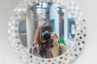 カメラに向かってポーズをとる鏡の前に立つ人の写真・画像素材[2706953]