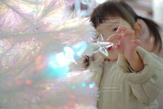 キラキラのクリスマスツリーに触れる女の子の写真・画像素材[4017186]