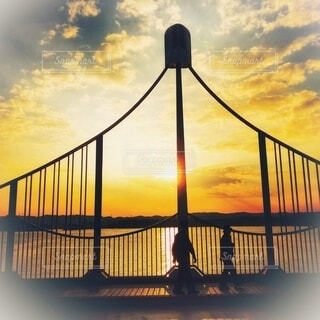 橋の向こう側から降り注ぐオレンジ色の朝日の写真・画像素材[4048095]