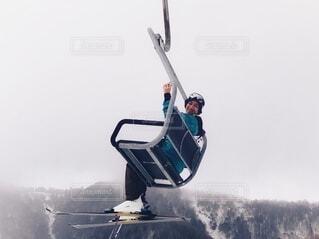 スキーリフトに乗りながら手を振るの写真・画像素材[4063803]