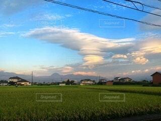 富士山の上にかかる何十もの傘雲と緑の田んぼの写真・画像素材[4083618]