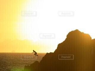自然,風景,海,空,屋外,太陽,ビーチ,雲,夕暮れ,水面,水平線,シルエット,岩,人,少年,飛び込み