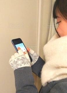 マフラーと手袋をしてスマホを見ている女の子の写真・画像素材[4064070]