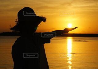 女性,自然,空,夏,夕日,絶景,屋外,太陽,南国,ビーチ,雲,夕暮れ,帽子,水面,海岸,沖縄,景色,シルエット,日没,観光,手のひら,美しい,逆光,人,旅行,トロピカル,太陽光,黄昏,夕陽,夏休み,久米島,沈む,映え,すくう,シンリ浜