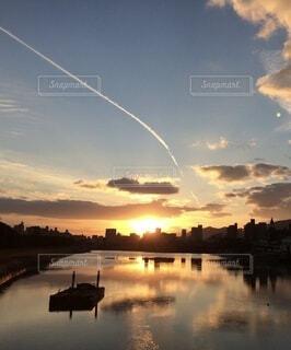 自然,空,屋外,太陽,雲,青,夕暮れ,船,川,水面,景色,反射,オレンジ,光,飛行機雲,陰影