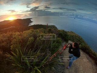絶景の夕日を、一眼レフカメラで写真を撮ろうとしている人の写真・画像素材[4243835]