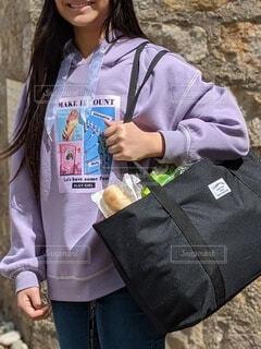 エコバッグを持ってレンガの壁の前にたたずむ十代女性の写真・画像素材[4417400]