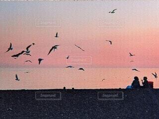 夕暮れの浜辺にたたずむふたりの写真・画像素材[4622875]