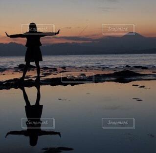女性,自然,空,屋外,太陽,ビーチ,雲,青,夕焼け,黒,夕暮れ,水面,海岸,影,反射,シルエット,女の子,オレンジ,人,旅行,旅,地平線,橙,逆さま,フォトジェニック,大の字