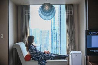 ソファーでくつろぎ窓の外を眺める女性の写真・画像素材[4285690]