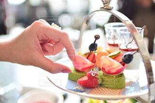 食べ物の皿を持ってテーブルに座っている女性の写真・画像素材[4291767]