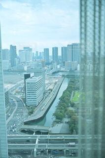 カーテンと窓越しに見える高層ビル群の写真・画像素材[4291768]