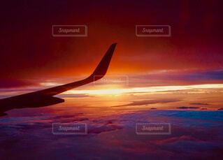 機内からの夕日と翼のシルエットの写真・画像素材[4090941]