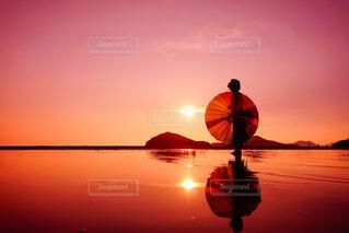 夕日と傘を持った女性のリフレクションの写真・画像素材[4100990]
