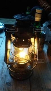 木製のテーブルの上のランプと酒の写真・画像素材[4091796]