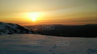 雪に覆われた斜面に沈む夕日の写真・画像素材[4091839]