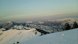 雪に覆われた山並みと朝焼けの空の写真・画像素材[4091870]