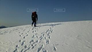 雪に覆われた斜面を登る男と青空の写真・画像素材[4091886]