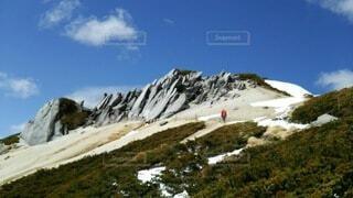 山の中腹を歩く人と青空の写真・画像素材[4091994]