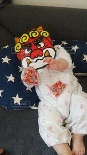 鬼のお面をつけて豆を撒く赤ちゃんの写真・画像素材[4116082]