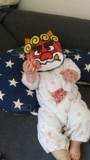 鬼のお面をつけて豆を撒く赤ちゃんの写真・画像素材[4116081]