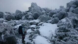 薄氷が張る岩の雪山と人の写真・画像素材[4144064]