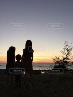 夕焼けを見つめるこども達の写真・画像素材[4104123]
