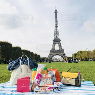 エッフェル塔を背景に草の中に座っている人々のグループの写真・画像素材[4353420]