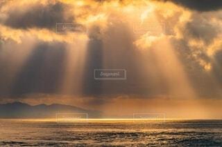 雲間から海に差し込むオレンジ色の太陽の光の写真・画像素材[4150277]