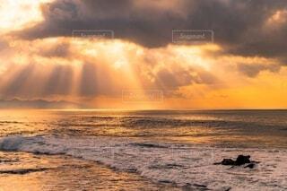 雲間から海に差し込むオレンジ色の太陽の光の写真・画像素材[4150275]