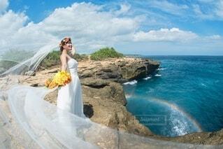 虹の出た海辺に立つ花嫁の写真・画像素材[4157371]