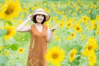 ひまわり畑に立つ笑顔の女性の写真・画像素材[4663853]