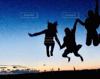 夕日を背景に空中に飛び込む男の写真・画像素材[4125010]