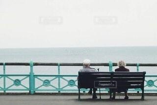 ベンチに座り、海を眺める老夫婦の写真・画像素材[4118514]