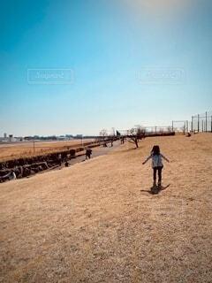 原っぱで走る娘の写真・画像素材[4136021]