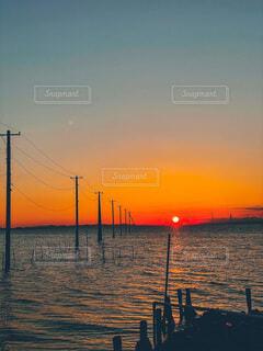 夕日と電信柱と海との写真・画像素材[4121690]