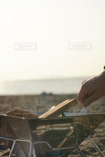 焚き火に焚べる手の写真・画像素材[4127093]