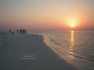 水平線に沈む夕陽と学生達の写真・画像素材[4133715]