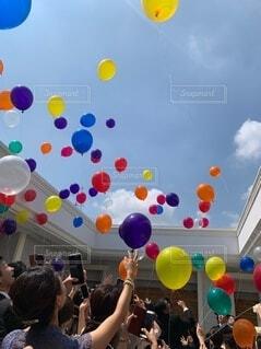 空に風船を飛ばす人々の写真・画像素材[4149159]