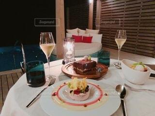 食べ物の皿とワイングラスをテーブルの上に置くの写真・画像素材[4379970]