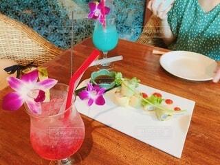 テーブルの上の飲み物と女性の写真・画像素材[4637333]