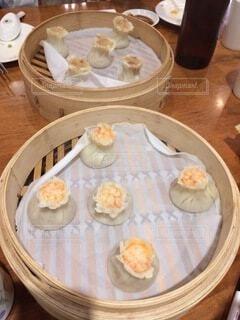 木製のテーブルの上に座っている食べ物のボウルの写真・画像素材[4154707]