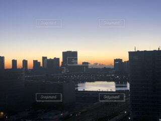 背景に都市がある水域に沈む夕日の写真・画像素材[4142823]
