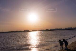 夕暮れに水辺で遊ぶ子供達の写真・画像素材[4148303]