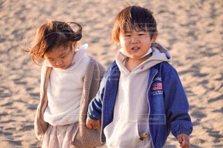 砂浜で妹の手を引く兄の写真・画像素材[4148301]